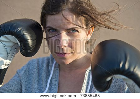 dynamic, natural and close up portrait of a young woman wearing boxing gloves her hair blowing in front of her face in the evening breeze