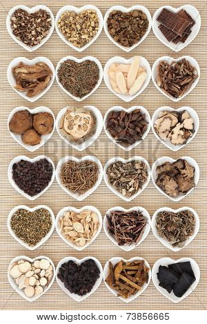 Large chinese herbal medicine selection in heart shaped porcelain bowls over bamboo background.