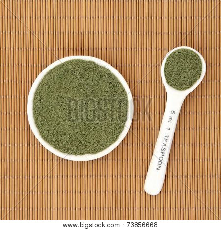 Moringa oleifera herb powder ayurvedic alternative medicine and superfood in a white porcelain bowl and measuring spoon over bamboo background.