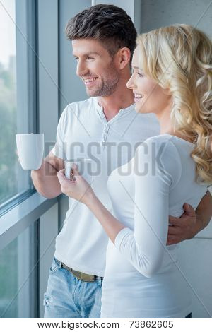 Young couple standing enjoying the view through a large glass window as they enjoy an early morning mug of coffee