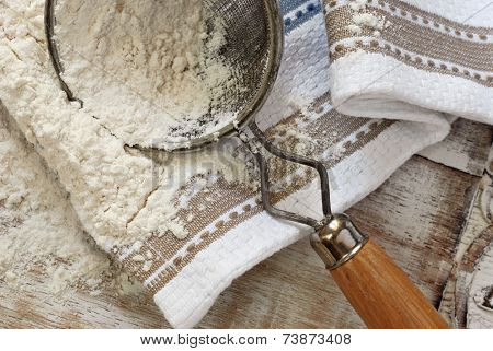 Rustic still life of baking flour with vintage sieve and kitchen towel on distressed wood.