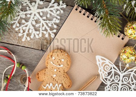 Christmas fir tree covered with snow, decor and blank notepad on wooden board background