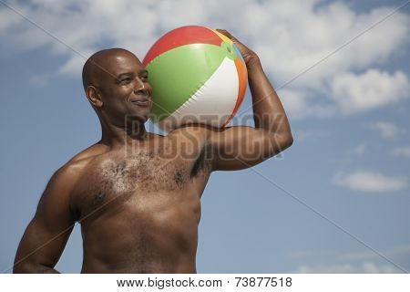 Portrait of African man holding beach ball