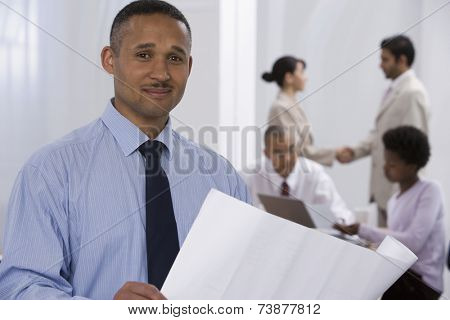 African businessman with co-workers in background