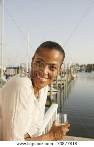African woman drinking wine on marina balcony