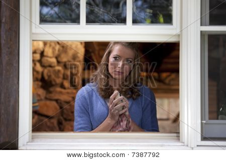 Crying Woman Drying Dish At Kitchen Window