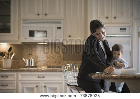 Hispanic mother on cell phone holding baby