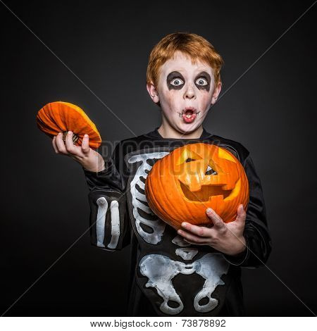 Surprised red hair kid in Halloween costume holding a orange pumpkin. Skeleton