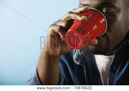 African man drinking from plastic cup