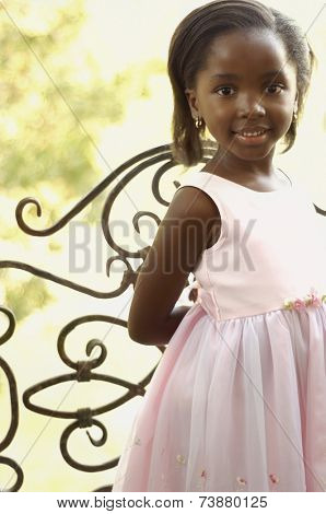 Young African girl smiling next to gate