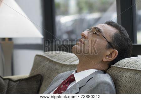 Hispanic businessman on sofa