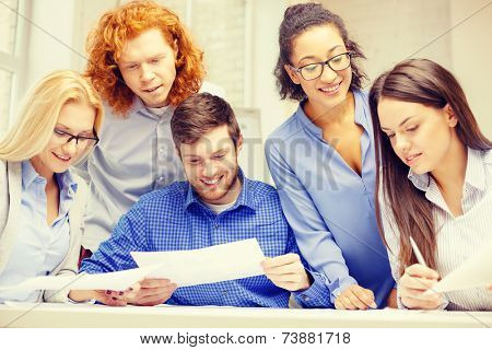business, office and startup concep - smiling creative team with papers working in office