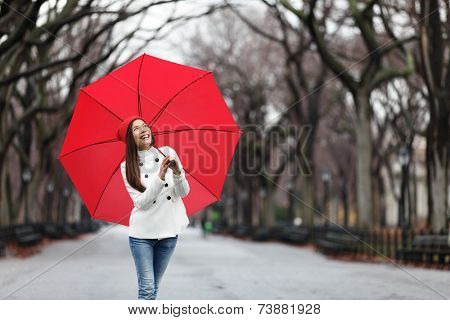 Woman with red umbrella walking in park in fall. Happy smiling multiracial girl walking cheerful with red umbrella in Central Park, Manhattan, New York City, USA.