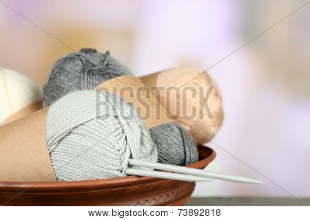 Knitting yarn with knitting needles, on light background