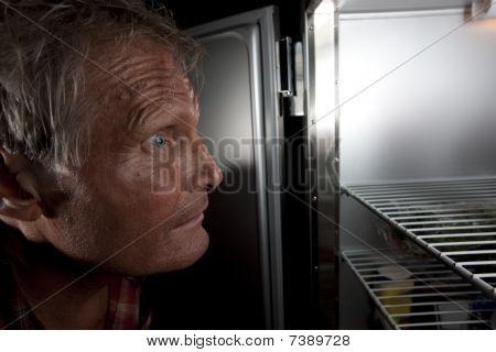intensive Mann starrt in Kühlschrank