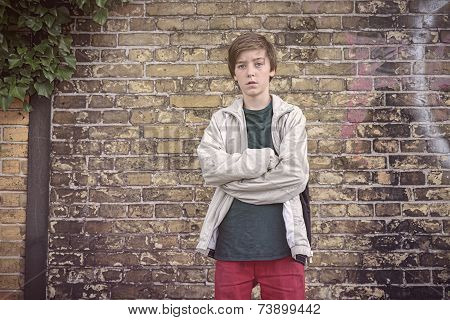 Portrait Of A Serious Teenage Boy With Crossed Arms