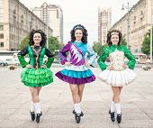 stock photo of irish  - Three women in irish dance dresses and wig posing outdoor - JPG