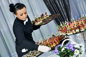 stock photo of catering service  - Waiter with meat dish serving catering table with food snacks during party event - JPG