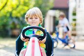image of pedal  - Active little blond toddler child driving pedal car in summer garden outdoors - JPG