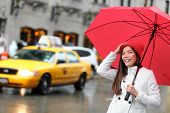 stock photo of rain  - New York City Manhattan woman with fall umbrella walking happy in streets downtown smiling with red umbrella in the rain with yellow taxi cabs - JPG
