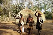 stock photo of zulu  - A Zulu chief and two warriors in a traditional village in South Africa - JPG