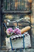 stock photo of wooden door  - Bicycle with picnic snack in wooden box on old wooden door background - JPG