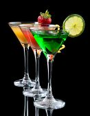 picture of cosmopolitan  - Three cocktails cosmopolitan cocktails decorated with citrus lemon twist yellow martini drink with strawberry isolated on a black background - JPG