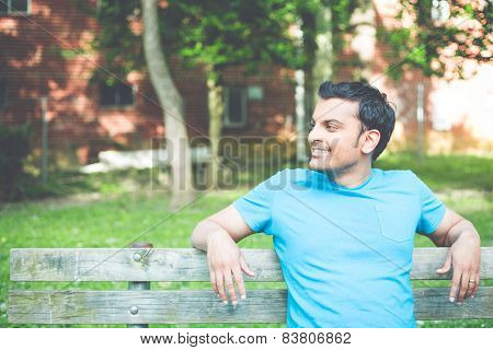 Man In Blue Shirt Chilling On Bench
