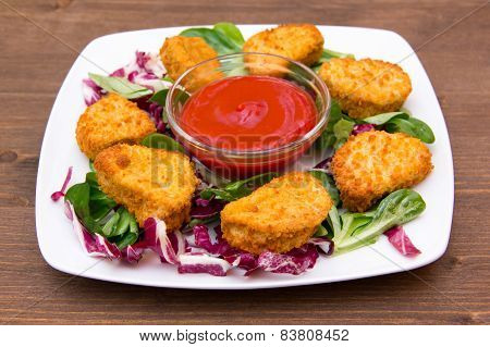 Nuggets of chicken over salad on wood