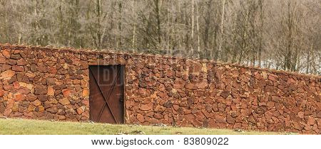 View Of Stone Fence With Door On Field.