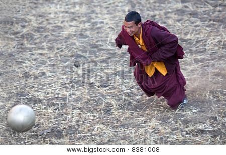 Young Buddhist Monk Playing Soccer