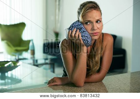 Young Woman With Toothache Putting Ice Bag On Mouth