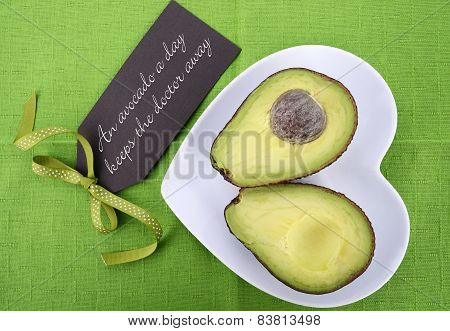 Avocado Cut In Half On Heart Shape Plate On Bright Green Tablecloth, With Message Greeting Tag.