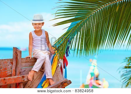 Cute Fashionable Boy Posing On Old Boat At Tropical Beach
