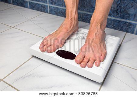 Female bare feet on bathroom scales