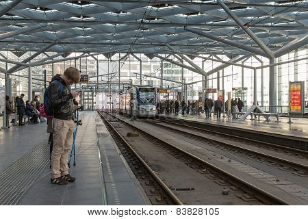 Travelers Waiting For The Tram At The Central Station Of The Hague, The Netherlands