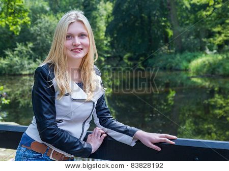 Blonde girl leaning on fence near water and trees