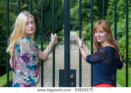 Two girls holding metal bars of entry gate