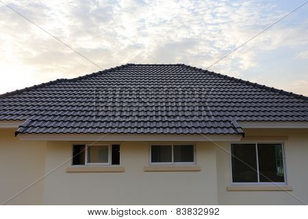 Black Tiles Roof On A New House With Sunset Sky