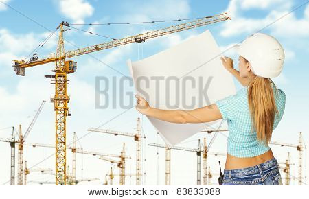 Woman in helmet standing backwards and holding paper sheet. Tower cranes as backdrop