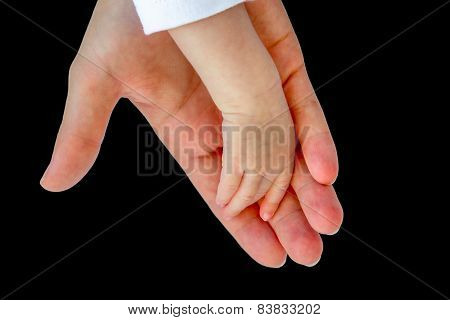 Hand of mother carrying arm of baby on black