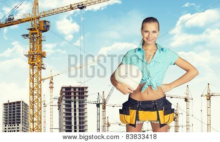 Woman in tool belt holding helmet under his arm. Looking at camera, smiling. Construction site as ba