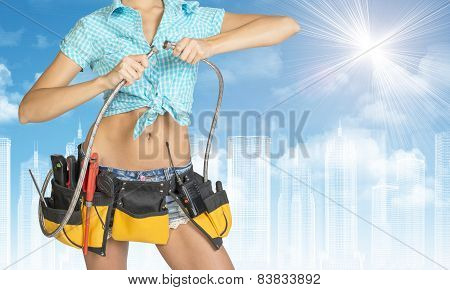 Woman in tool belt, connects two flexible hose. Cropped image. Wire-frame buildings as backdrop