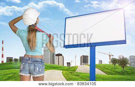 Woman in helmet stands backwards. Looks at billboard. Green hills with road and buildings as backdro