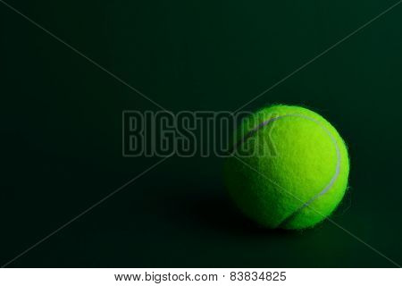 Single Tennis Ball On Green Background