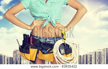 Woman in tool belt standing akimbo. Cropped image. High-rise buildings as backdrop