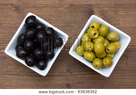 Bowls with green and black olives on wood from above