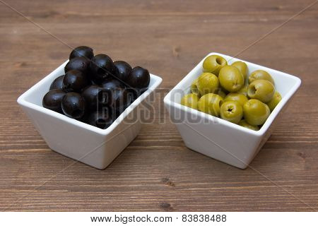 Bowls with green and black olives on wood