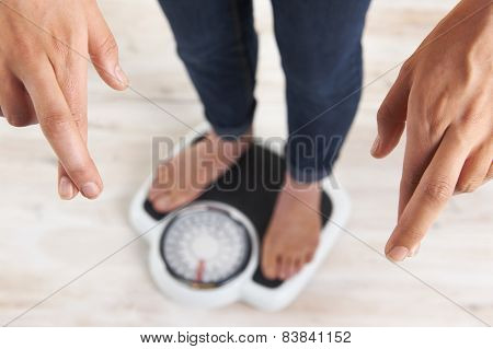 Woman Standing On Scales With Fingers Crossed