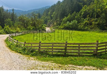 Winding country road with old wooden fence and green meadow